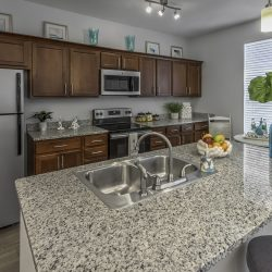 A kitchen with dark cabinets and granite countertops.