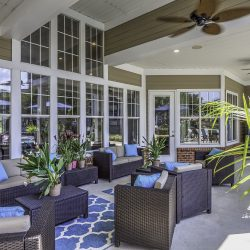 A comfortable covered patio with ceiling fans, palms, and chairs.