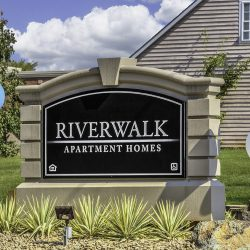 The beautiful sign at the entrance to the Riverwalk Apartments.