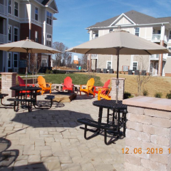 A half circle of chairs sits around a fire pit at the Riverwalk Apartments.