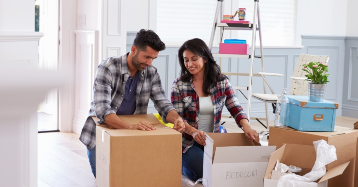A man and woman unpack their boxes in a new space.