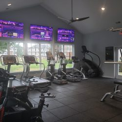 A selection of exercise equipment with TVs in front.