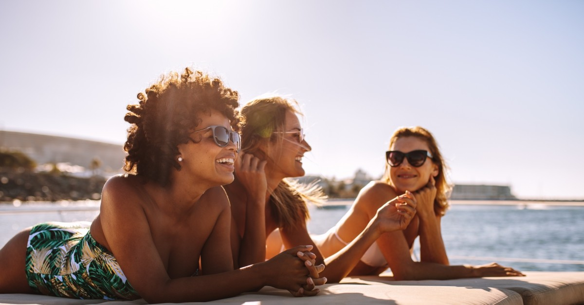 A group of women smile and sunbathe together.