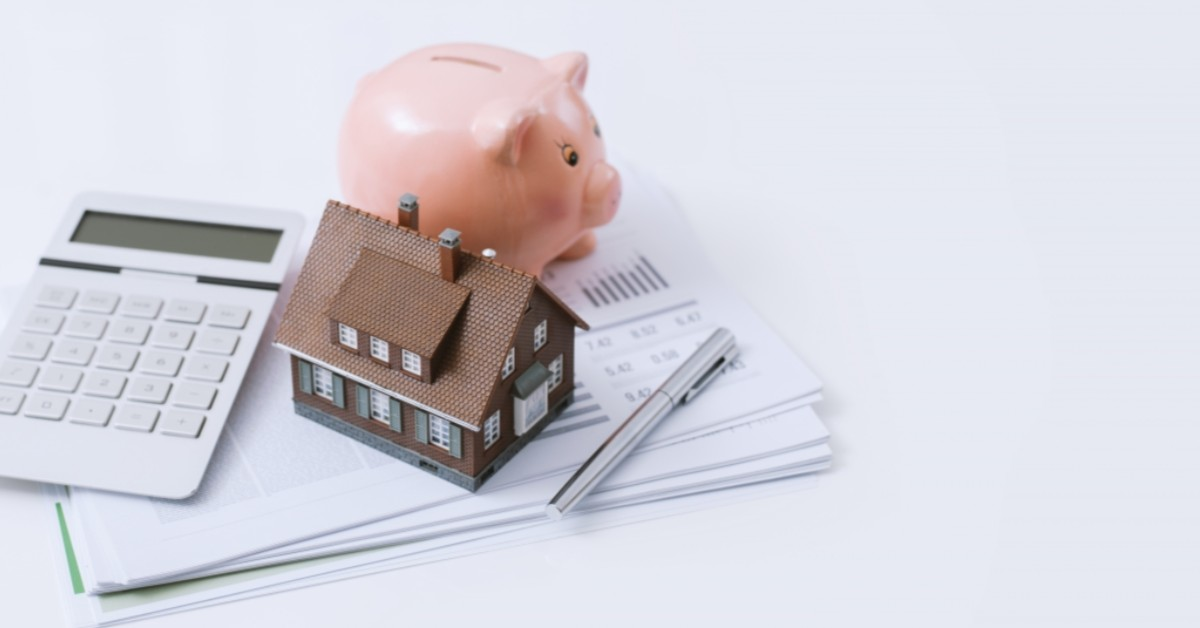 A piggy bank, model house and calculator rest on top of a packet of paper.