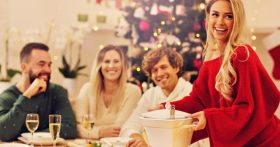 A group of people eat at a table with a Christmas tree in the background.