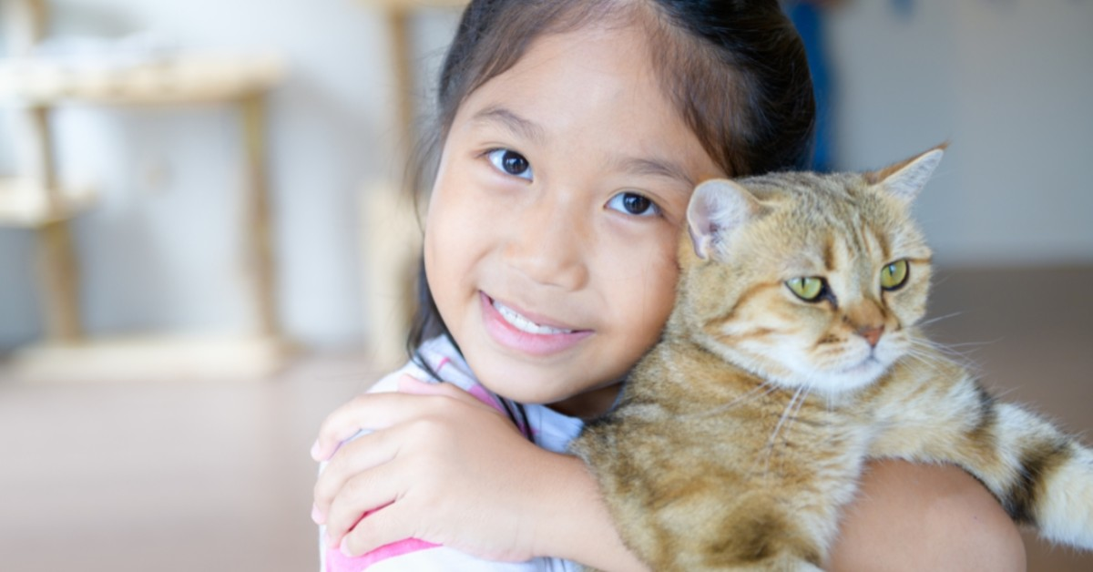 A young girl hugs a cat to her.
