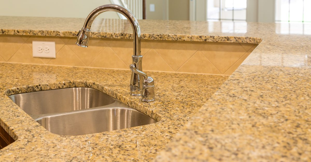 Stainless steel sink in tan granite countertop - Robins Plumbing Inc.