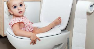 """Toddler playfully stuck in the toilet, looking towards the camera for blog """"Bathroom Safety for Children"""""""