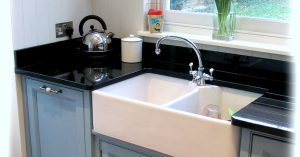 Kitchen with white sink, blue cabinets, and black counters - Robins Plumbing Inc.