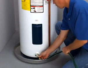 A plumber attaching a hose to a water heater - Robins Plumbing Inc.