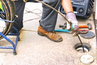 A plumber guiding a sewer inspection camera into a pipe - Robins Plumbing Inc.