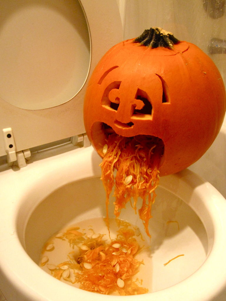 """Carved pumpkin """"throwing up"""" the insides on a toilet (sick pumpkin)"""