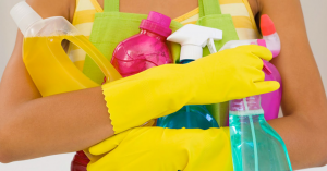 """Cover photo of person holding many cleaner bottles for blog """"Water Heater Cleaning and Water Heater Descaling"""""""
