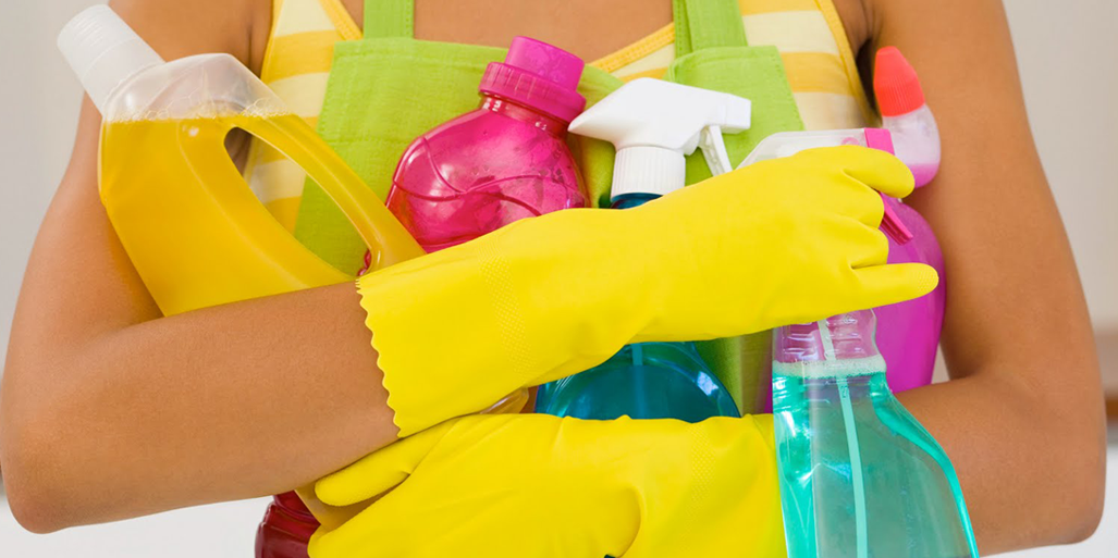 "Cover photo of person holding many cleaner bottles for blog ""Water Heater Cleaning and Water Heater Descaling"""