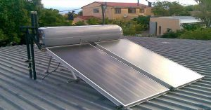 A solar hot water heater panel on top of a roof