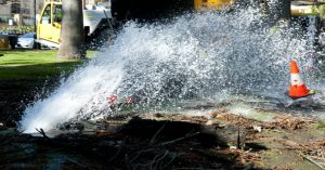A burst pipe spraying water onto a city street