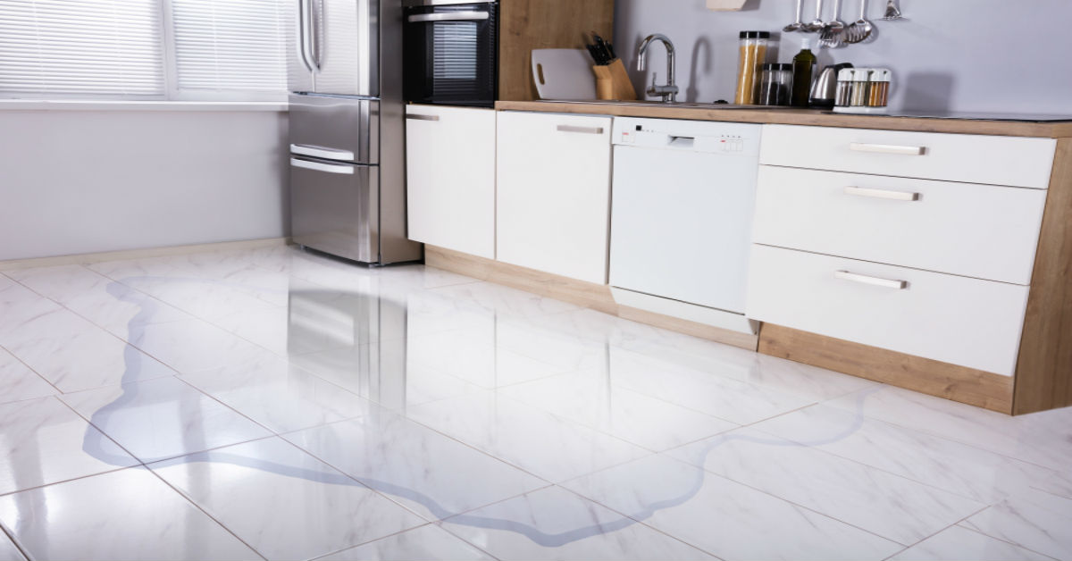 A clean white kitchen with a water puddle on the floor