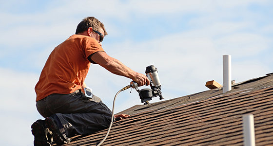 Worker Using Nailgun on Shingle Roof