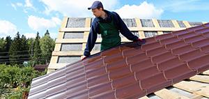 Worker Installing Metal Sheet Roofing