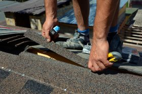 local roofer's hands repairing shingles