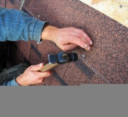roofer nailing shingle in place