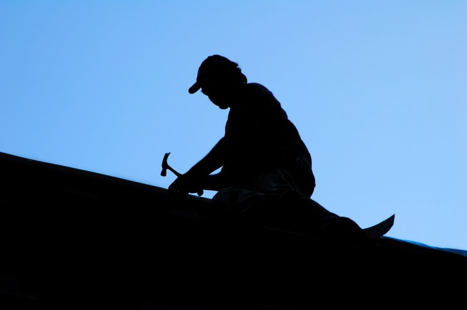 silhouette of roofing contractor against blue sky
