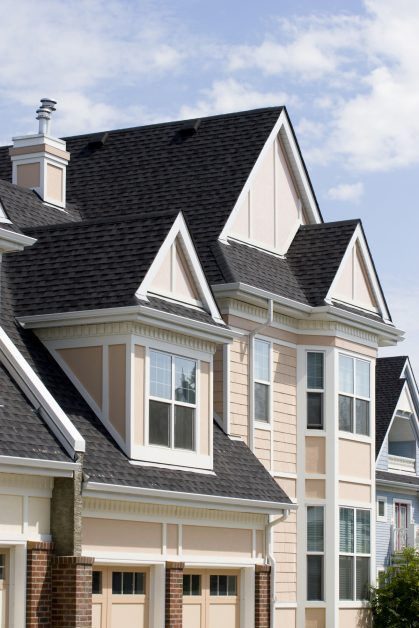 asphalt shingles on roof of brick-and-cream colored house against blue sky