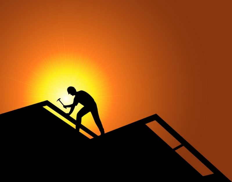 silhouette of roofer against sunshine