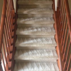 narrow stairway with white carpet is steam cleaned