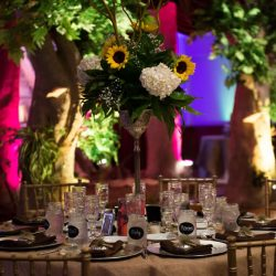 Decorated table with flower arrangement and a Royal Palace Ballrooms event