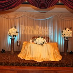 Yellow head table at wedding reception at Royal Palace Ballrooms