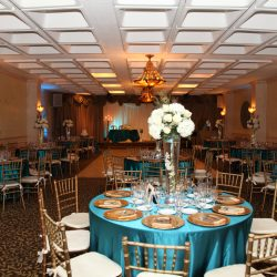 Wedding reception with blue tables and white flowers at Royal Palace Ballrooms