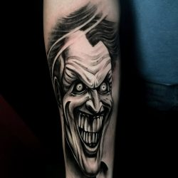Black and grey realism tattoo of the Joker on the right forearm.