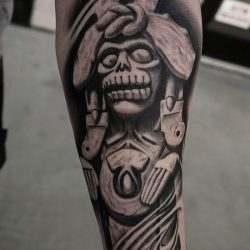 Black and grey realism tattoo on forearm of an Inca statue with a skull face.
