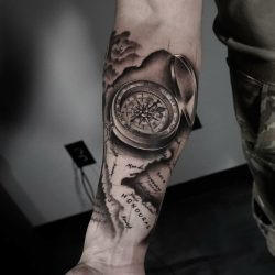 Black and grey realism tattoo of a compass and map on the right forearm.