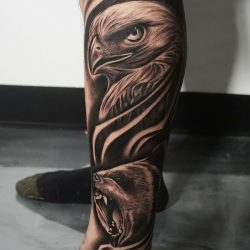 Black and gray realism tattoo of an eagle and bear on the left leg.