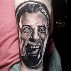 Black and grey realism tattoo of classic Hollywood horror Christopher Lee' Dracula portrait on forearm.