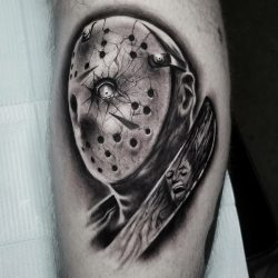 Portrait of Jason Voorhees in the hockey mask with a machete black and gray realism tattoo on the left leg.