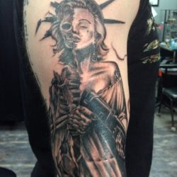 Black and gray tattoo mash up of Marilyn Monroe and skeleton of Lady Liberty holding a rifle.