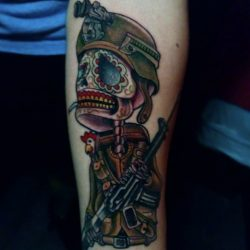 Neo-traditional tattoo a Day of the Dead skull soldier wearing night vision with a chicken and a M4. Placed on the forearm.