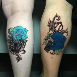 Couples traditional tattoo idea of a lock and key. Blue roses, heart lock, skeleton key in color with a black and grey blend.