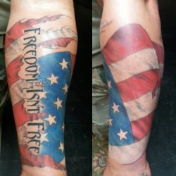 "All American tattoo ""Freedom Isn't Free"" in full color with American flag stars and stripes that wraps around forearm."