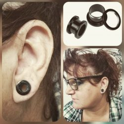 Double zero gauge piercing with black stainless steel tunnels.