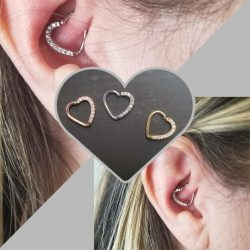 Daith piercing with a 16 gauge heart-shaped hoop with 9 CZ stones.