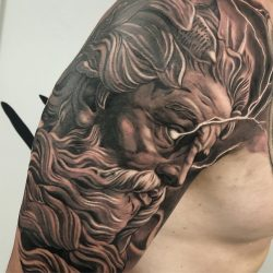 Black and gray realism tattoo of Zeus with lightning coming from the eyes on the right arm.