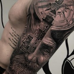Old shore man with a lighthouse, clock, and compass in the background. Black and gray realism tattoo.