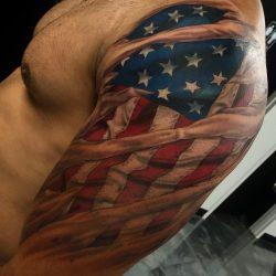 Full color patriotic tattoo of an American flag ripping through the skin on the left arm and shoulder.
