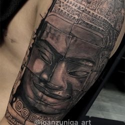 Custom tattoo in black and gray of an Olmec statue smiling.
