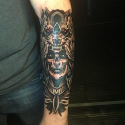 Traditional black and grey tattoo, female with warpaint in wolf headdress on the right forearm.