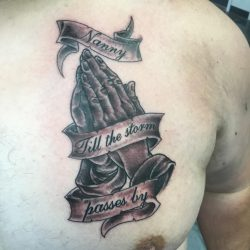 Traditional black and grey tattoo of praying hands with memorial banner. Located on the left pectoral.